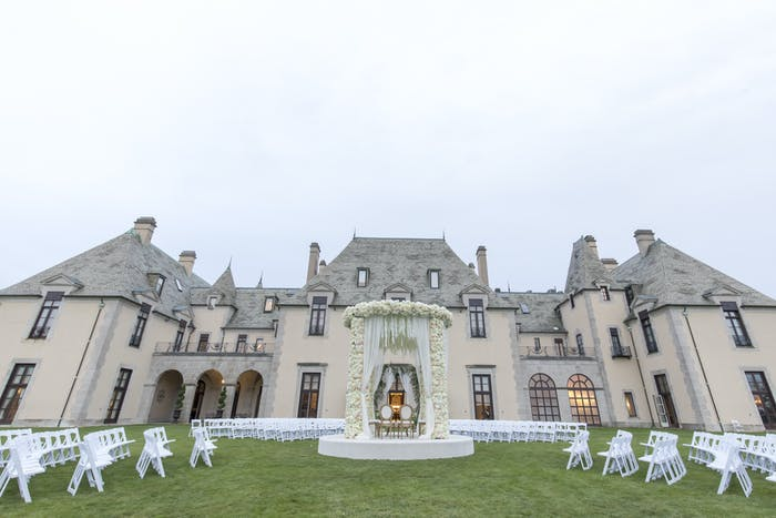 A massive castle with tables and chairs on the manicured grass
