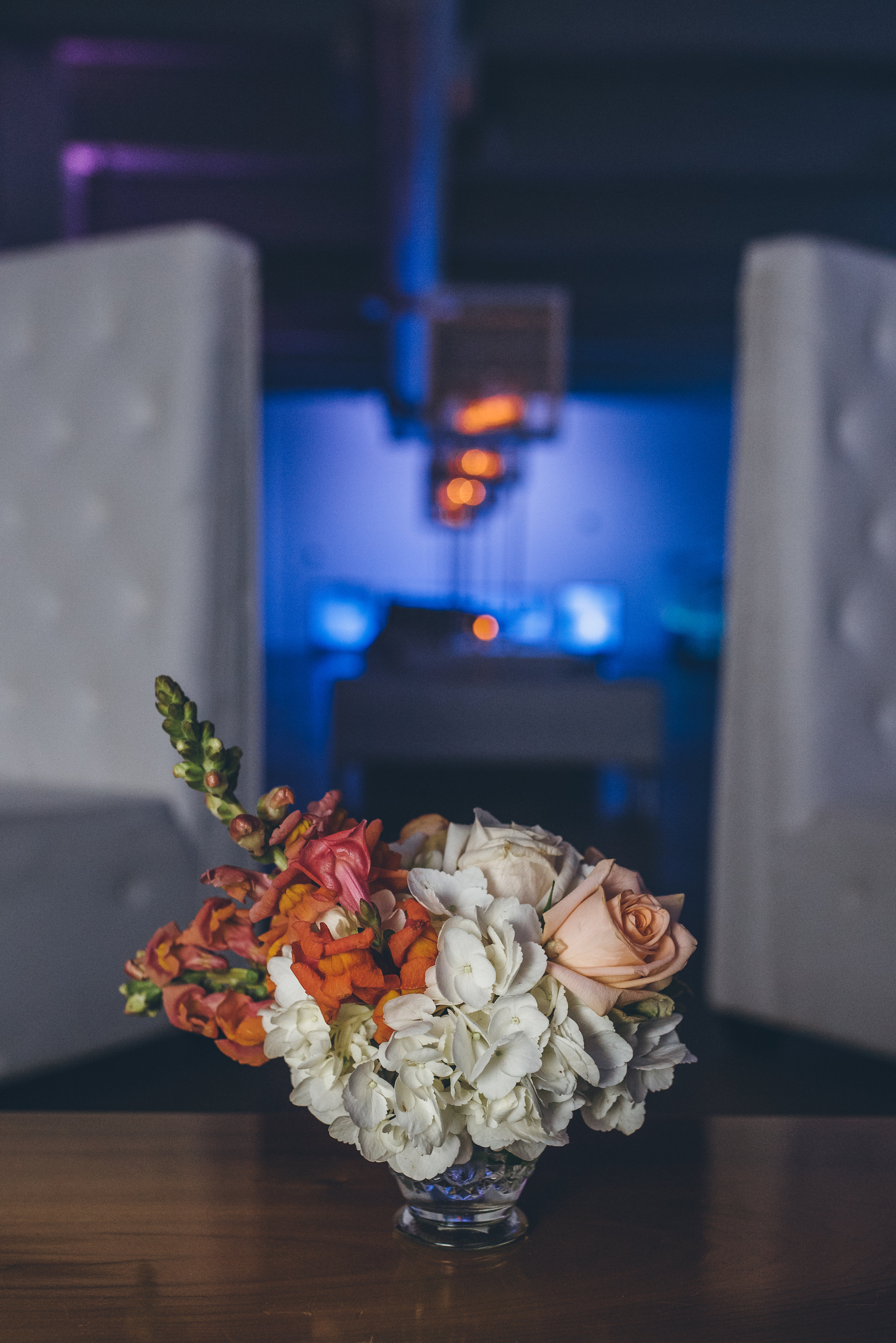 Inspired by spring, to soften the modern lines of Venue One. A colorful petite arrangement, highlighted by the romance of candlelight.