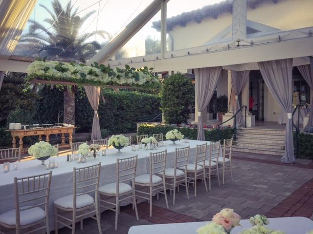 Chivari chairs beneath a gorgeous floral chandelier