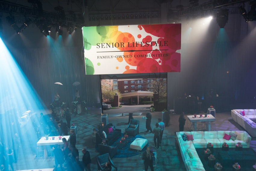 Large branded chandeliers hung from the ceiling highlighting the properties of Senior Lifestyle Corporation.