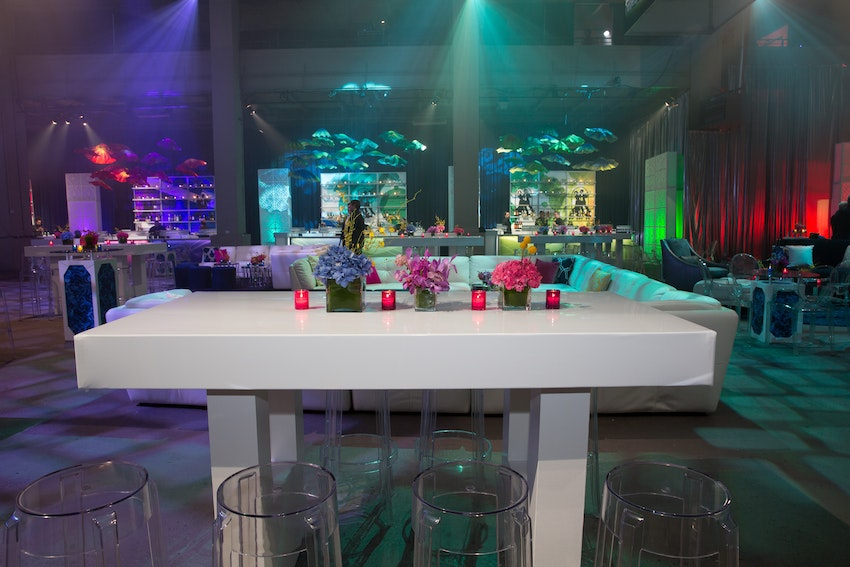 White hightop tables with clear acrylic bar stools created a dining space for guests at the Senior Lifestyle Corporation event.