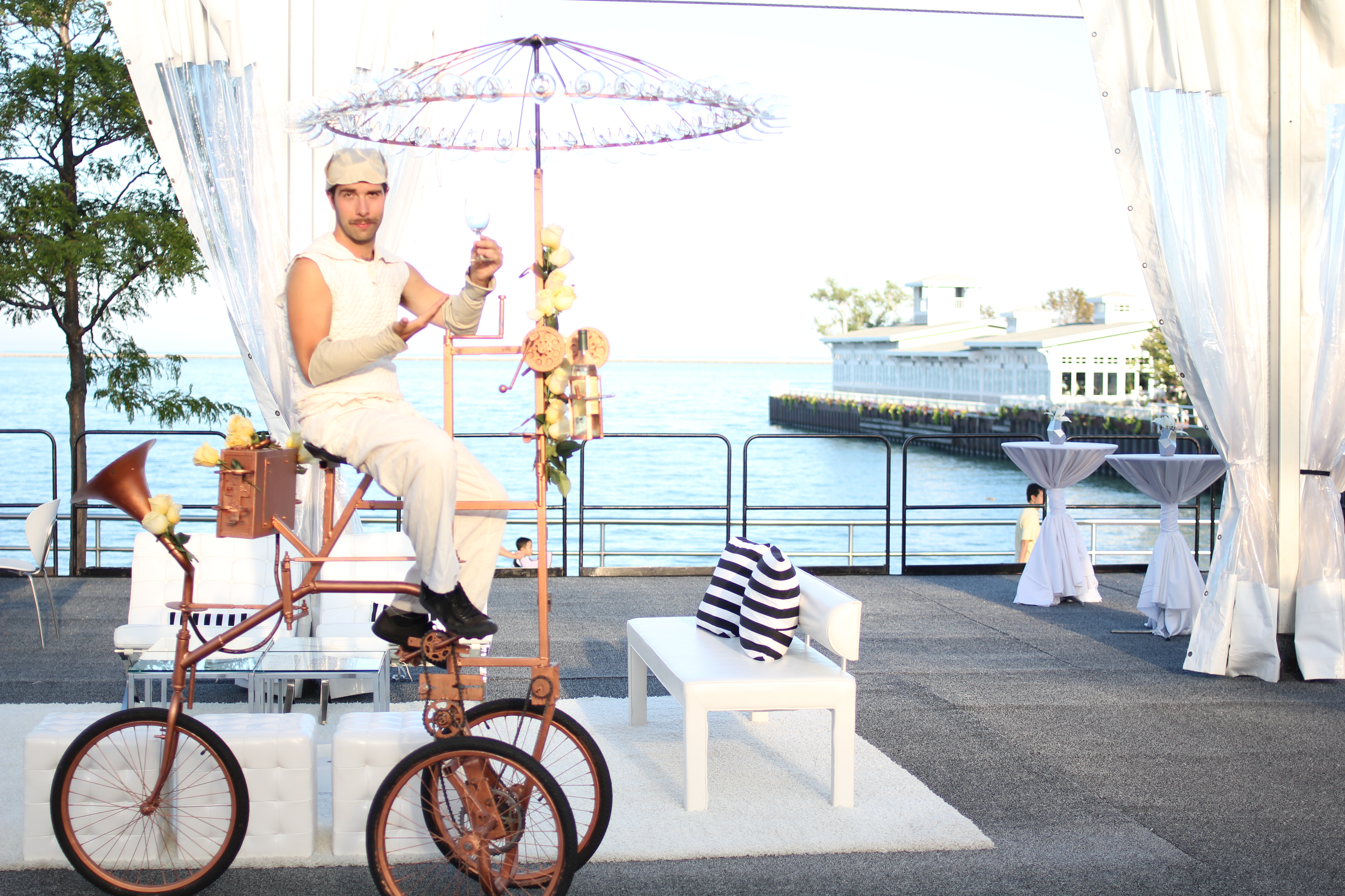 Impress your guests with this custom pedal-powered bicycle, which provides surprising and spectacular wine, juice or sparkling water service. A chandelier of stemmed glassware spins above the head of a rider, who works with exquisite precision as a series of mechanical interactions pour wine into a waiting glass.
