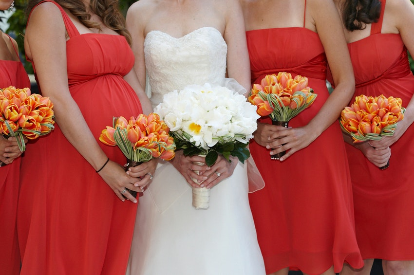 This brides bouquet is made up of delicate white tulips and accented with the bridesmaids harmonious orange tulip bouquets.