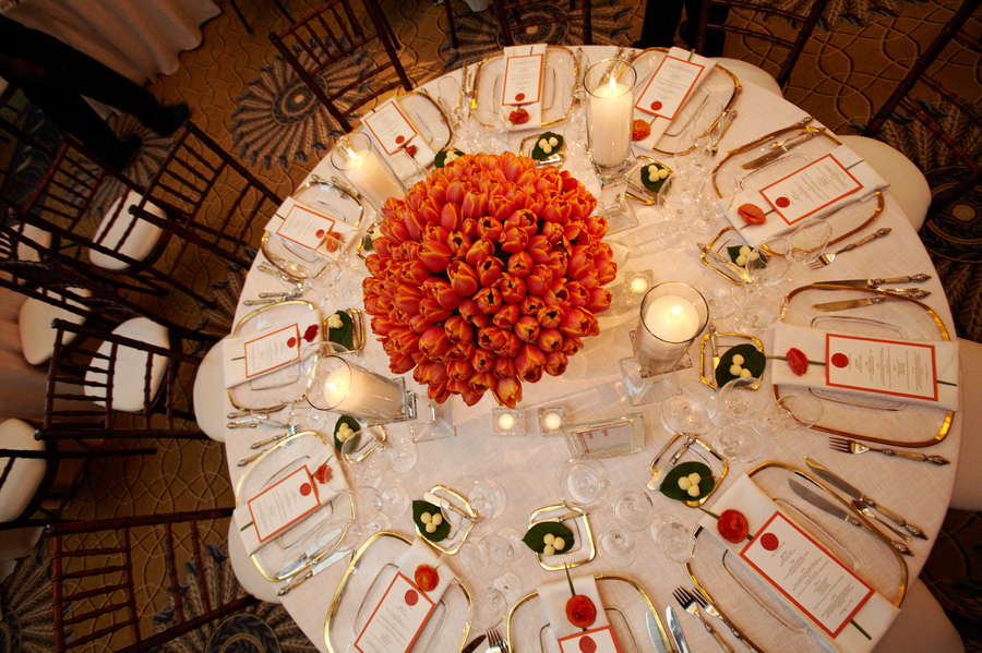 A bold centerpiece full of orange tulips radiates energy in the candlelight.