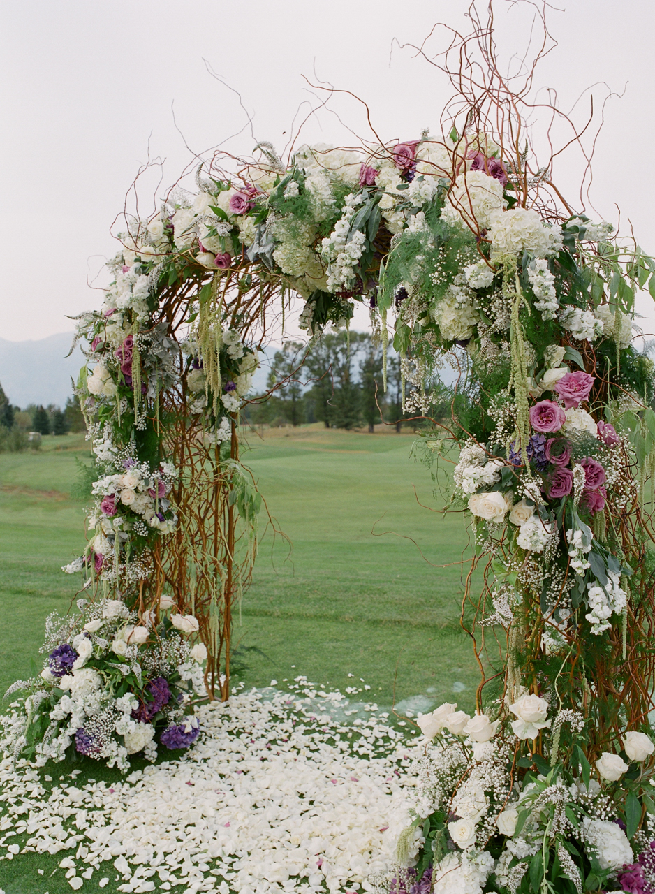 This arbor canopy was carefully created with an abundant variety of curly willow branches, baby's breath, blush roses, lavender rosemary, and other greenery for a perfect lush and natural ceremony.