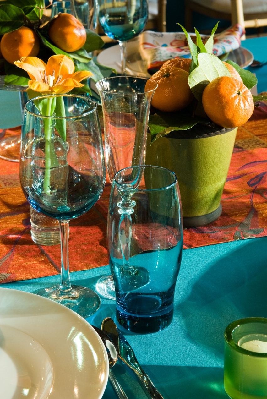 A close up shot of statement turquoise blue glassware paired with eclectic citrus centerpiece.