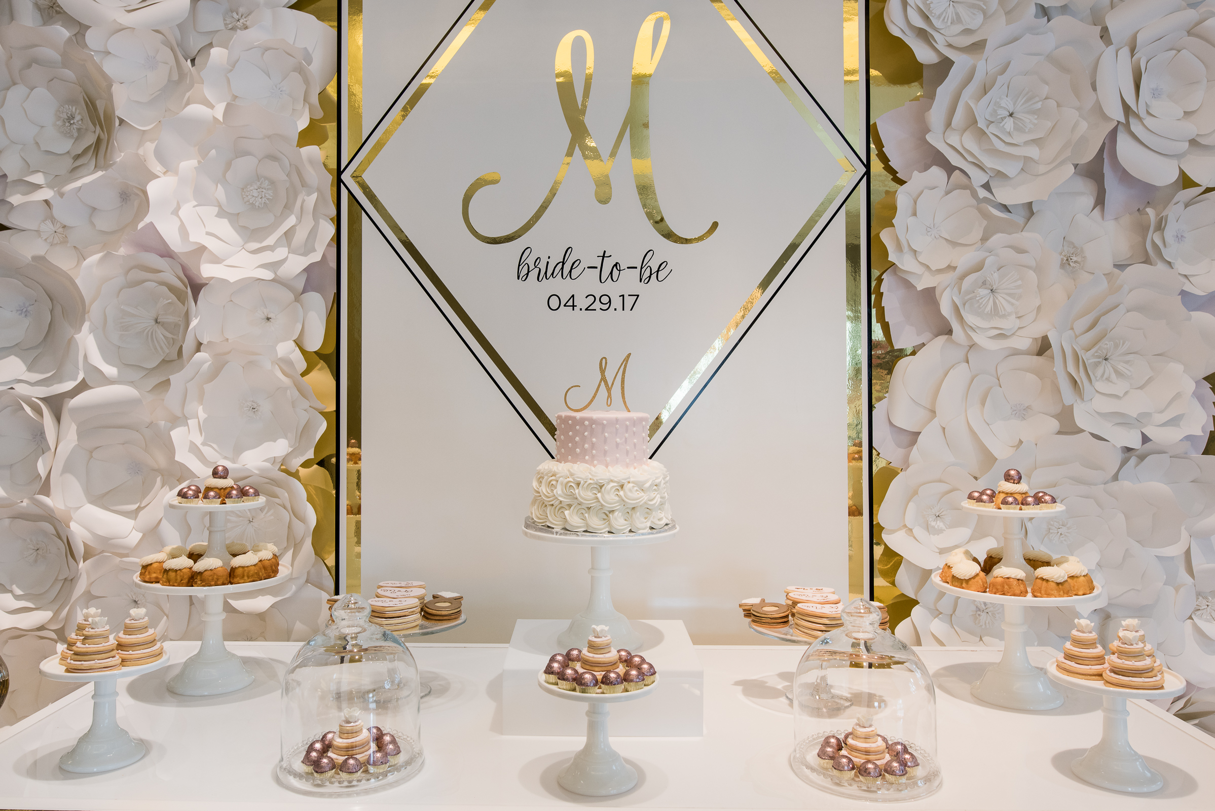 The magnificent dessert display of sweet treats with a custom backdrop of gold etched wall panels personalized with a large 'M'(the bride-to-be's first initial) and shower date. The engraved backdrop was bordered by enlarged paper white floral walls