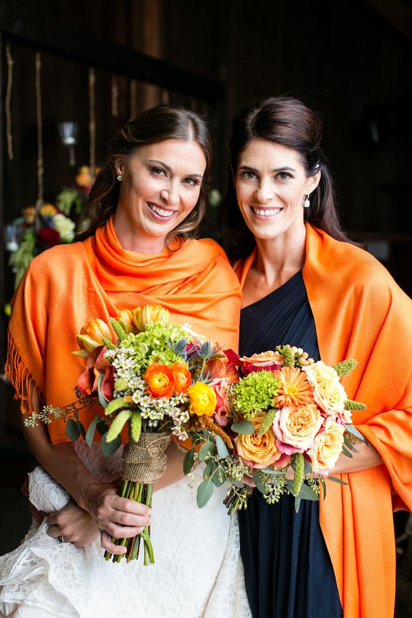 bride and bridesmaid in navy and orange