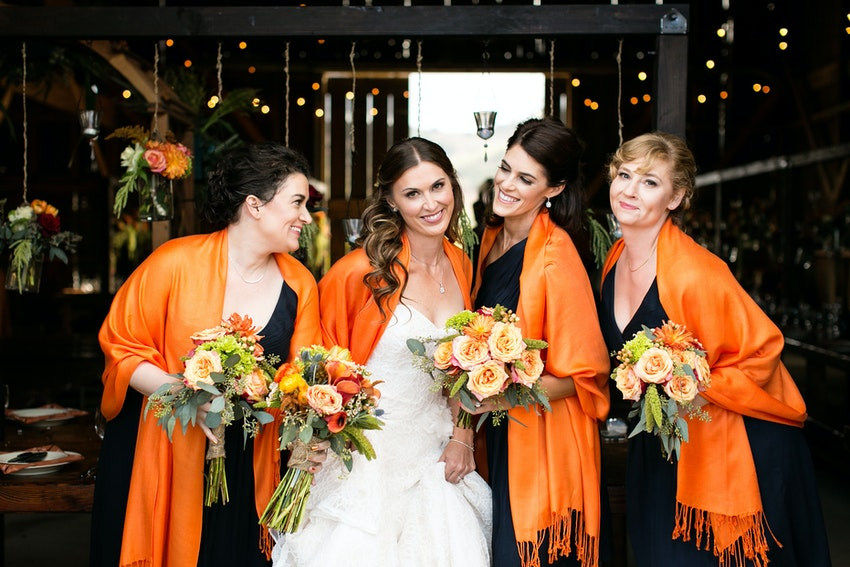bride and bridesmaids in navy and orange