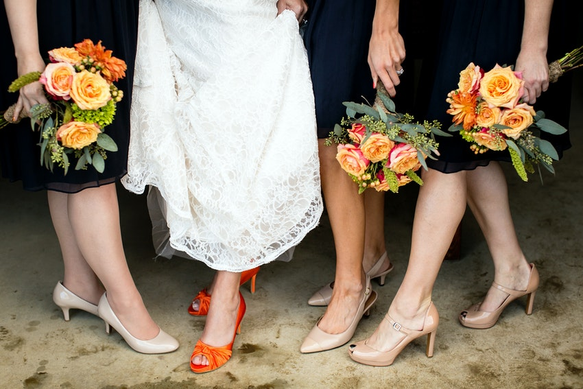 details of bride and bridesmaid shoes with bouquets