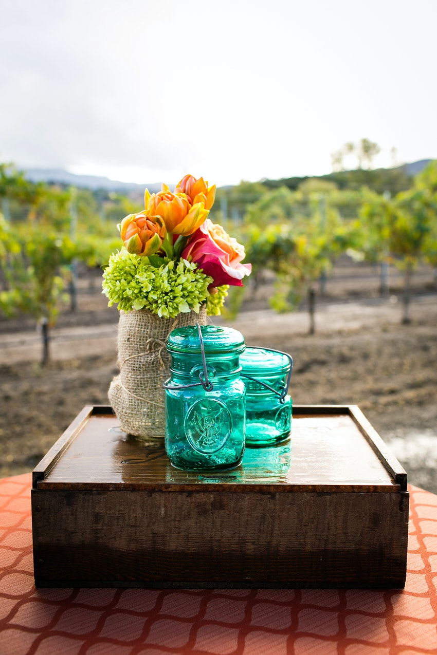 reception decore orange and green flowers with mason jars