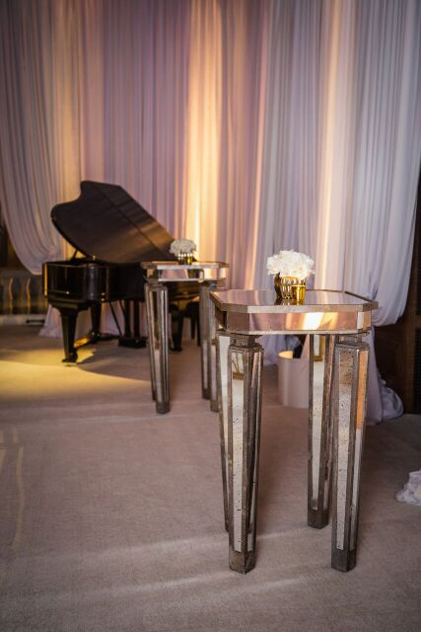Mirrored cocktail tables accompanied by a gorgeous baby grand piano.