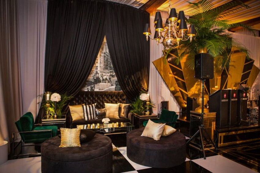 Glamorous cocktail lounge complete with a black tufted velvet sofa with matching ottomans lit by a gold and black chandelier