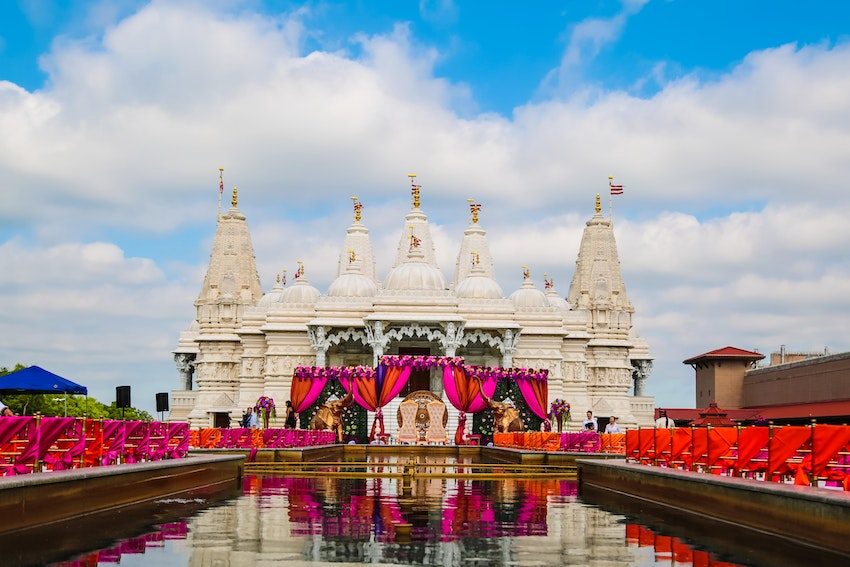 Outdoor hindu ceremony with open boxwood mandap set outside the gorgeous BAPS Mandir in Chicago. This bright color pallet consisted of orange, hot pink, and hint or green and purple. The water fountain sets the perfect ambiance for an outdoor ceremony.