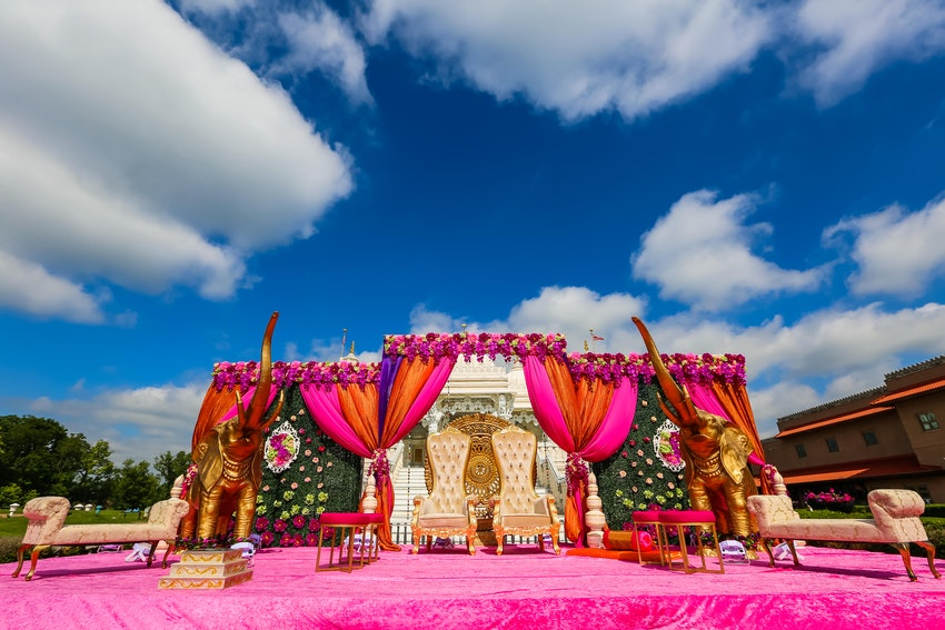 Outdoor hindu ceremony with open boxwood mandap with bright color scheme. The mandap was adorned with 8 feet tall statues of royal gold elephants and 6 ft tall royal throne chairs.