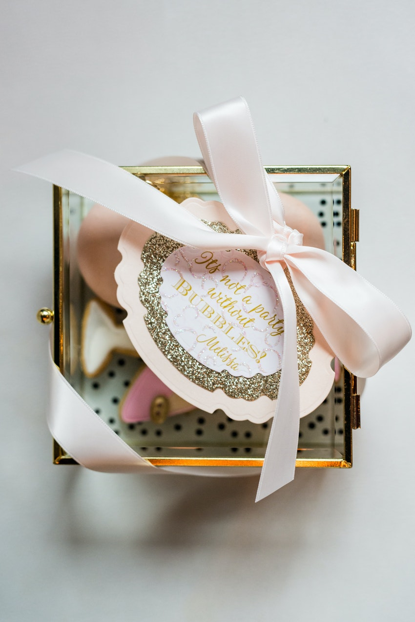 A goody box with elegant treats for each couple to take home. Creative quotes from the guest of honor sealed each parting gift. The cookies inside were pink and gold; cut in the shape of the guest of honor's favorites; a champagne flute, high heel and perfume.