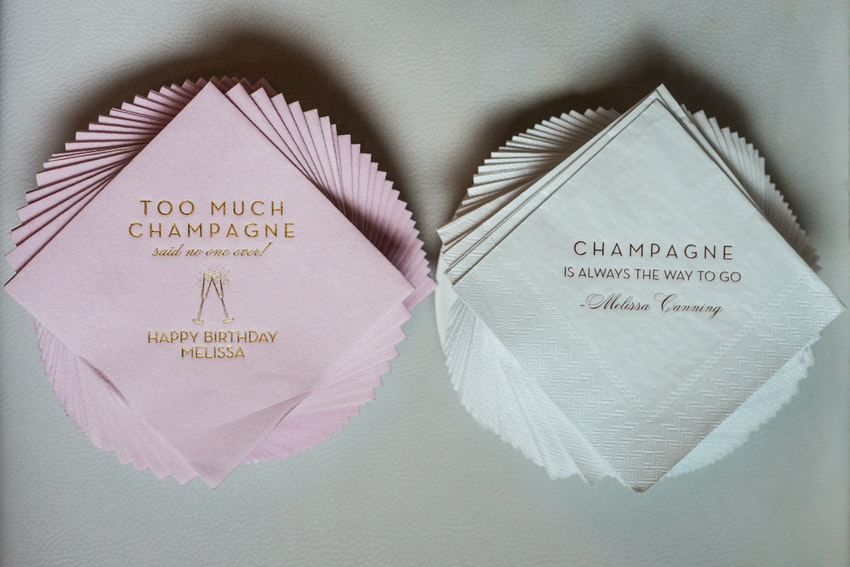 Personalized napkins in gold script held quotes and decals of champagne catch phrases.