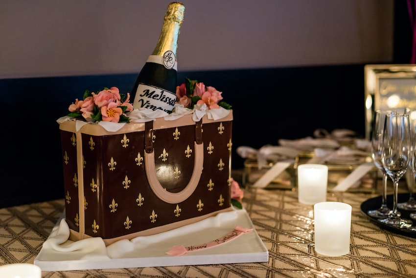 A replica of a Louis Vuitton bag holding a life size bottle of champagne and florals. The cake was a piece of art!