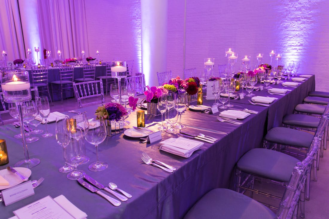 a purple lit room with rectangle long tables with purple linens and purple flowers