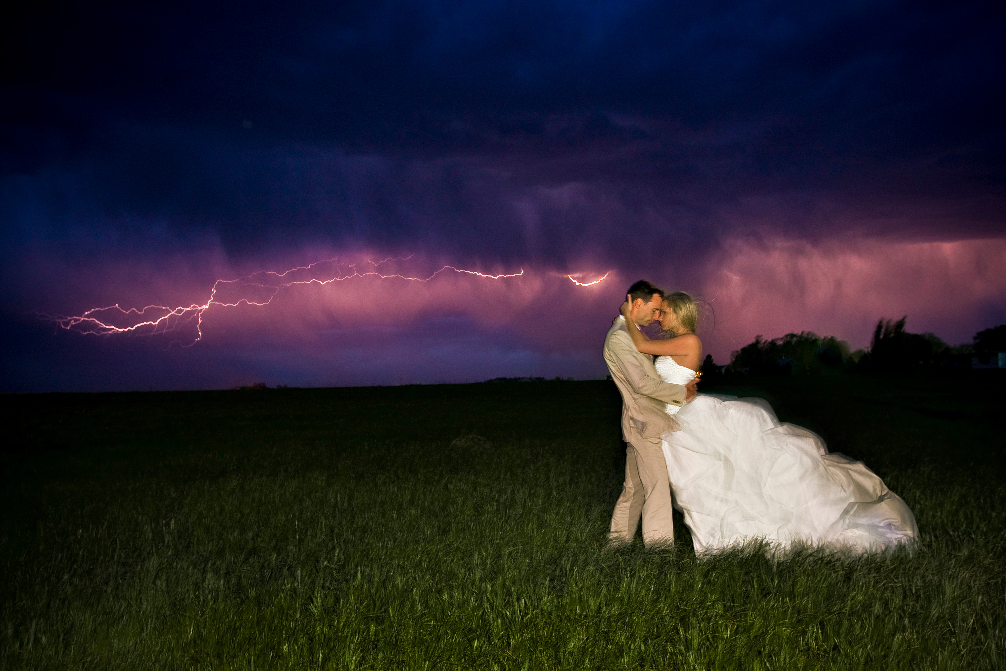 Bride in Groom with lightning in the distance.