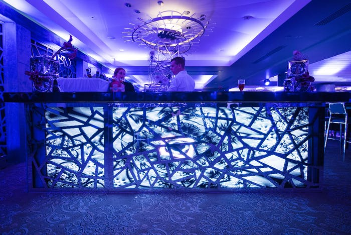an icy looking bar in the foreground. the ceiling of a ballroom in the background. The whole scene is lit up purple.