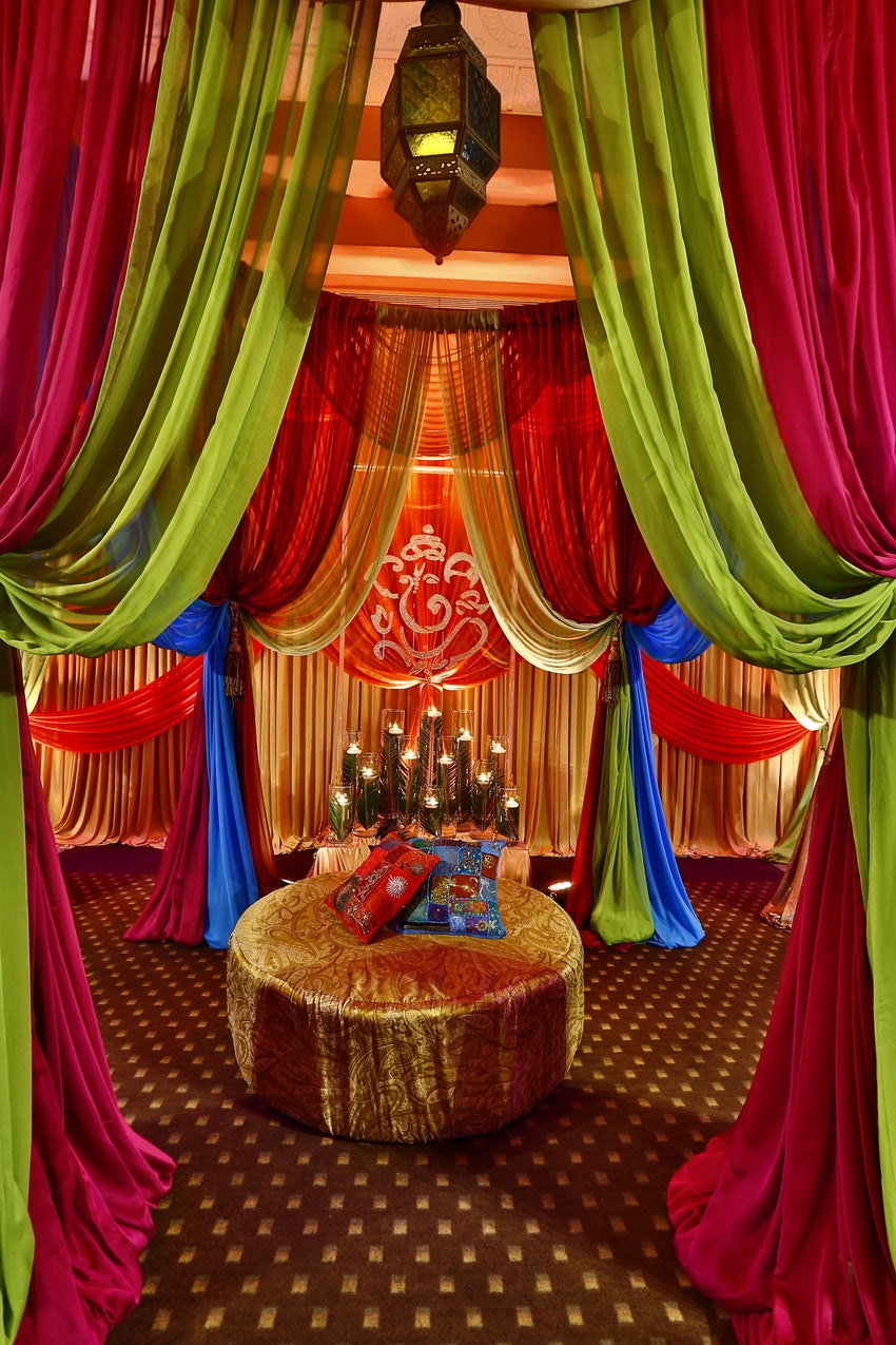 A magnificent and very colorful birthday party celebration with key elements such as elephants, umbrellas, lanterns and vibrant drapery.