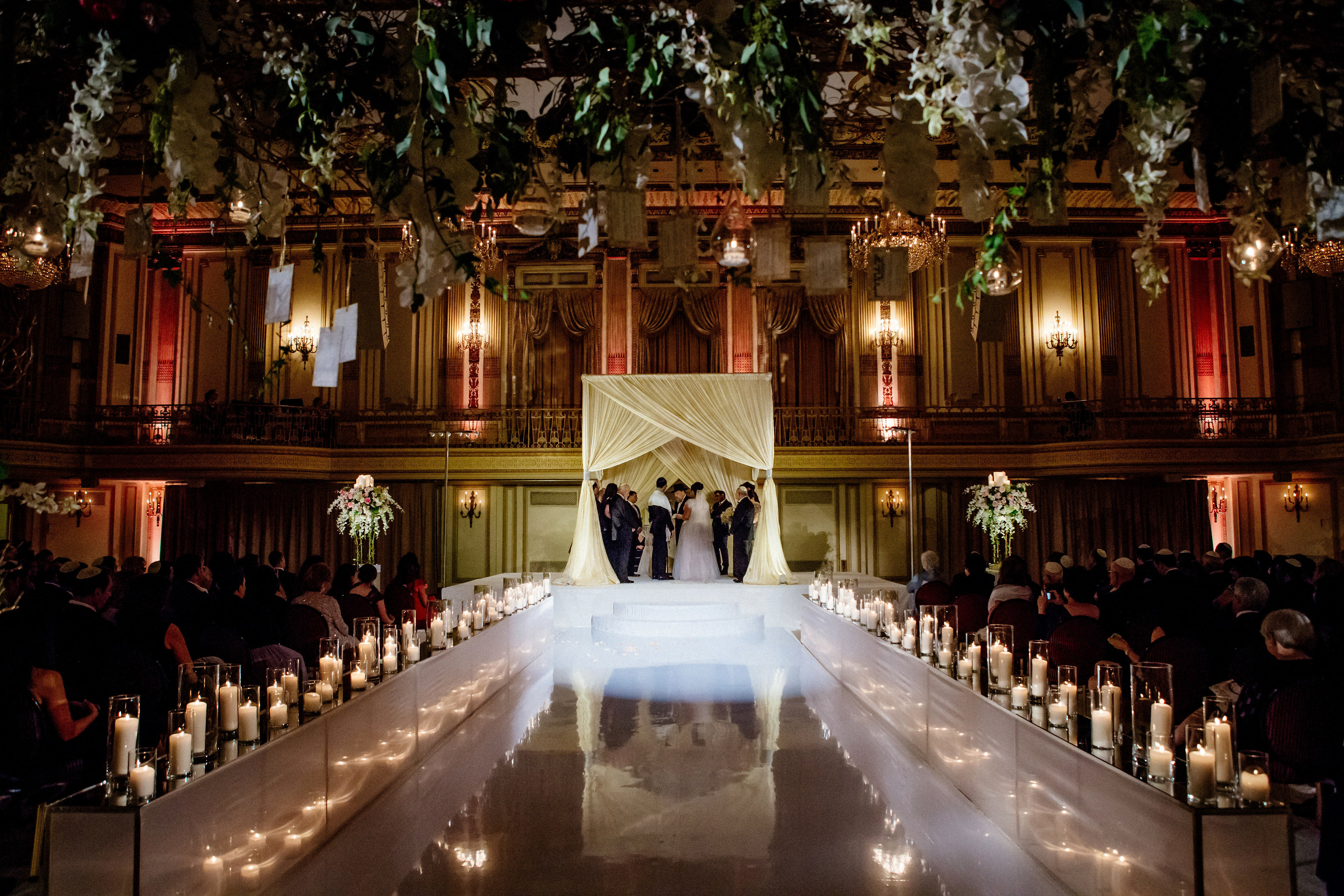 Chuppah decor features a criss cross front and back design with bone mirror fabric tied with Swarovski cuffs. The wishing arch is dressed with gold manzanita branches with white/ivory fresh floral and greenery. Small water drop accents are also included.