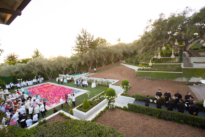 Waiters greeted the guests entering the cocktail hour with flutes of champagne as they gathered around the floral filled pool.