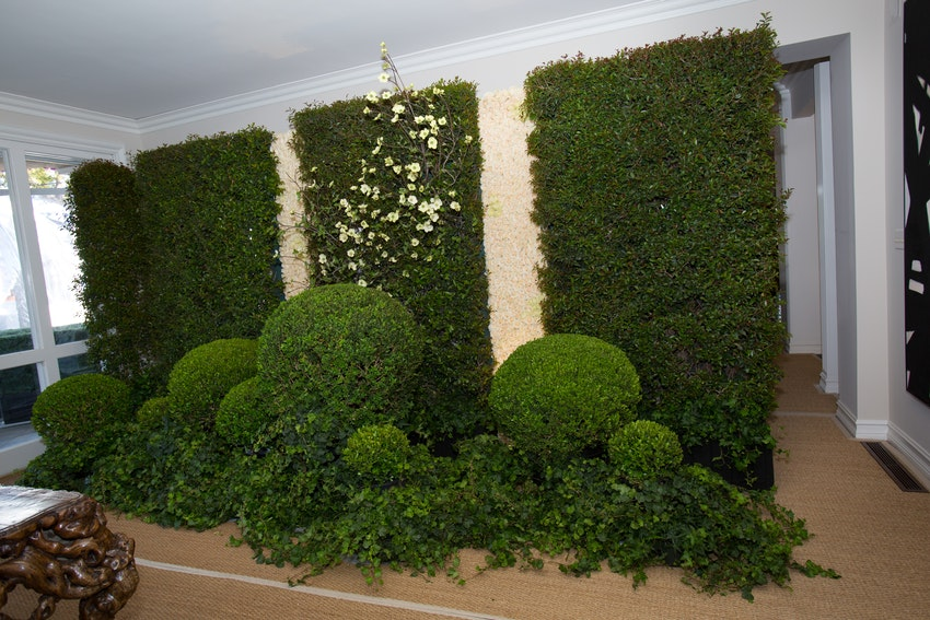 Elegant greenery and floral wall aligning the entrance way of the cocktail hour.