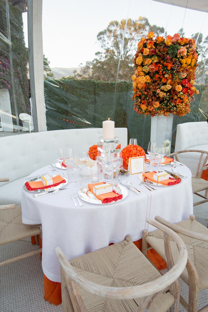 Orange, red, and white floral arrangements with glass candle treatments on each dining table made for an elegant display.