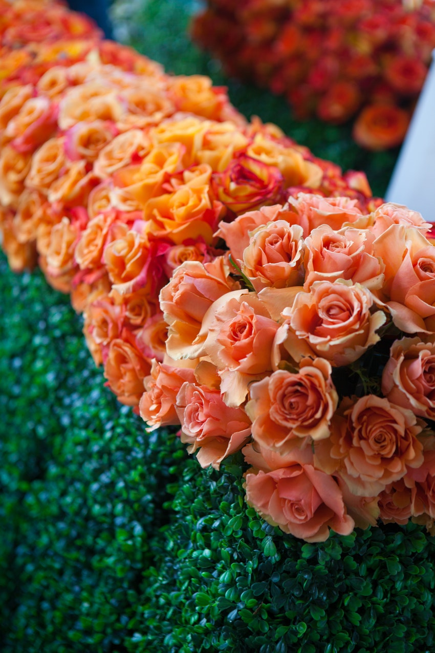 Elegant greenery and orange floral arrangements ties in with event decor colors.
