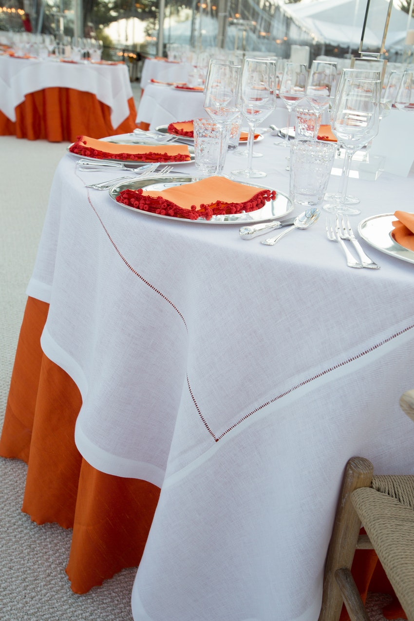 Beautiful white linen overlay the lamour orange linen on the dining tables during the reception.