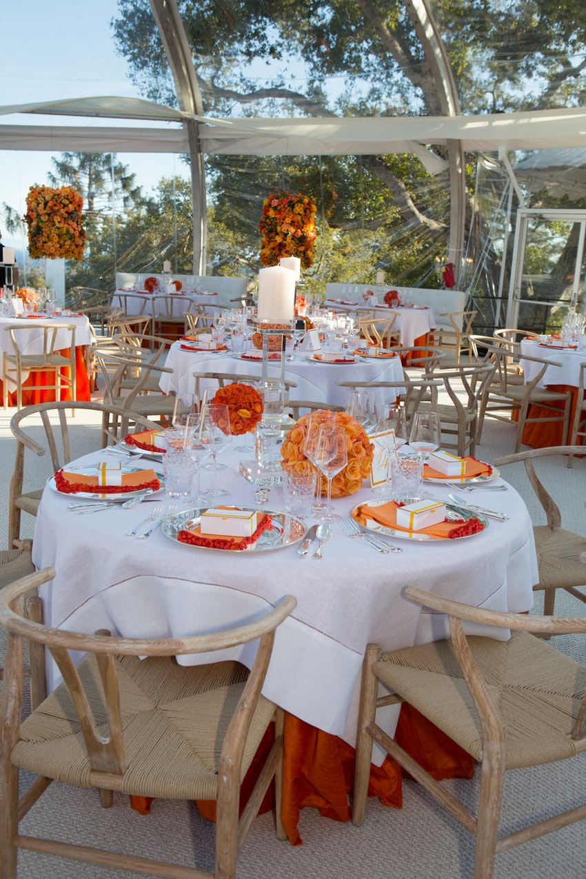 Gorgeous dining table arrangements with glass candle treatments and elegant orange florals.