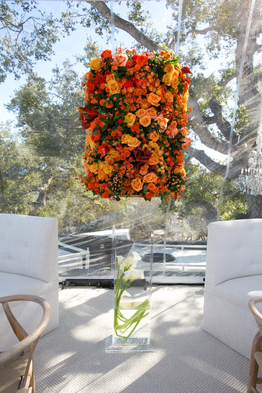 Lush orange and burgundy floral arrangement on top of a acrylic glass cylinder to tie in the decor colors.