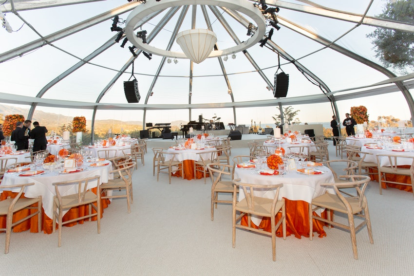 Dining tables, dance floor, and stage under a custom round tent overlooking Montecito, California.
