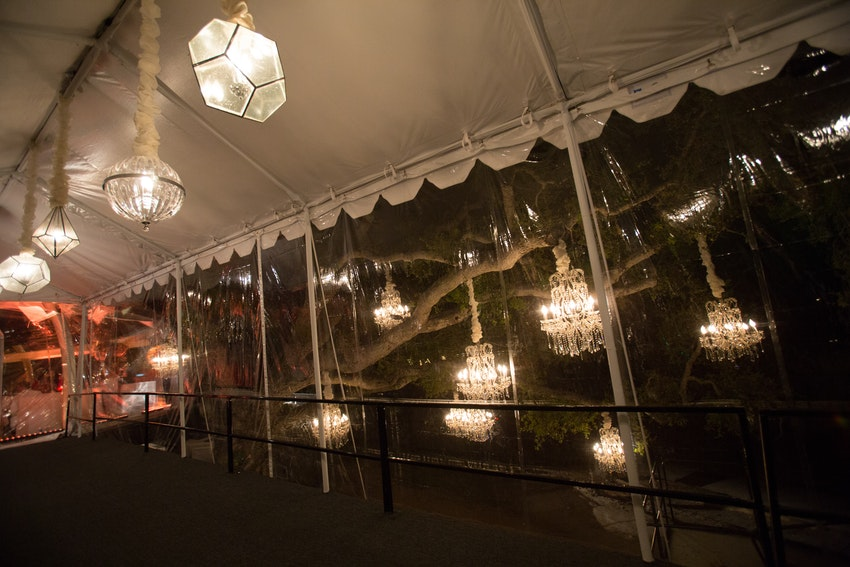 Hanging glass chandeliers aligned the ceiling of a covered tented hallway from the dining area to the afterparty.