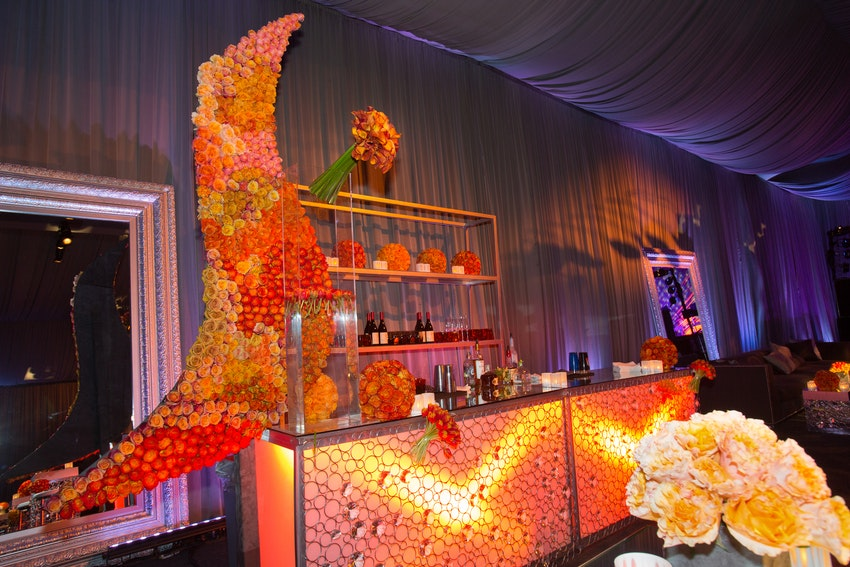 Gold brass back bars paired with orange illuminating bars with elegant adjourning floral arrangements at the afterparty.
