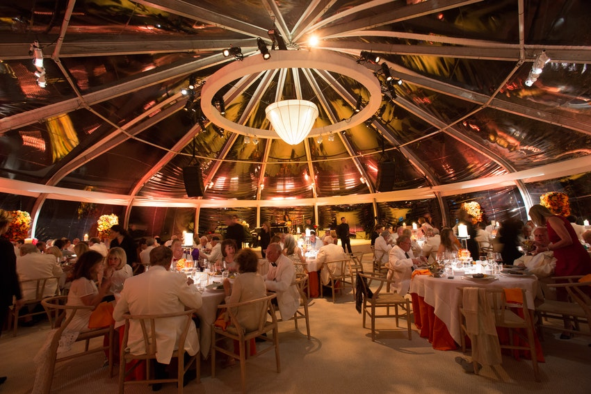 The orange uplighting and crystal chandelier brightens this custom round tent as the sun goes down.
