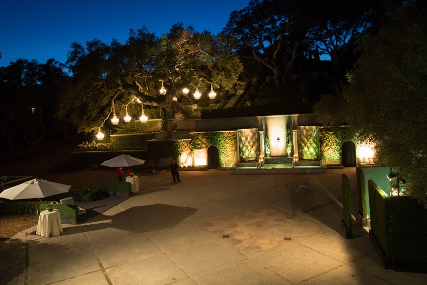 Illuminating glass chandeliers hanging from the trees and bright uplighting of this private estate created an elegant entrance way as guests arrived.
