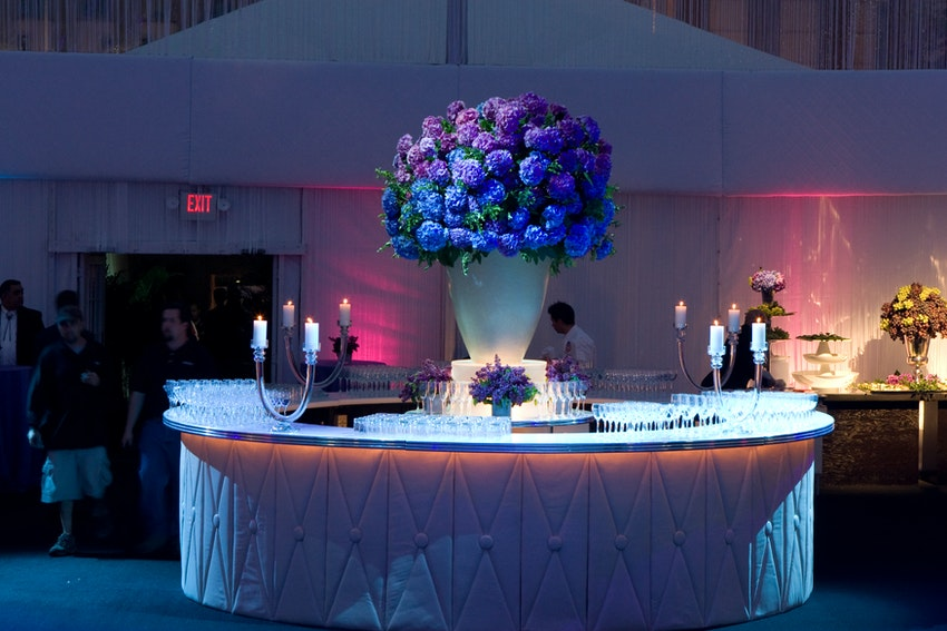 Purple hydrangea's in a gorgeous white vase was the focal decor for this large center white custom bar.