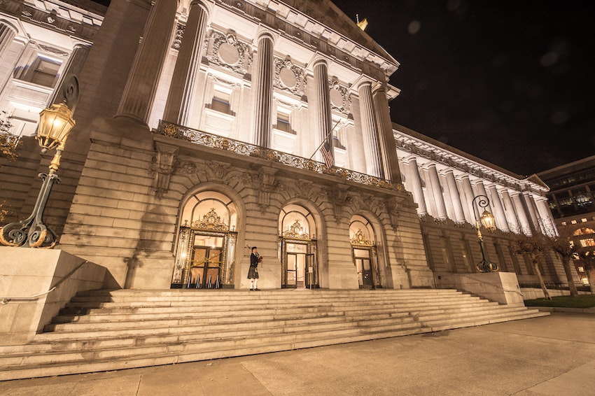 Exterior of San Francisco City Hall at night with lone bagpiper welcoming guests.