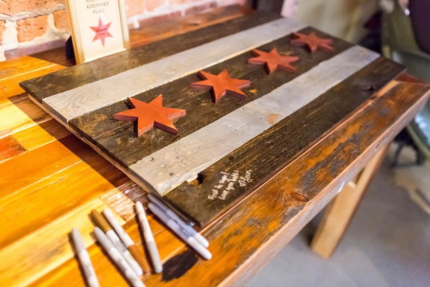 "Instead of a guest book, guests sign the ""Chicago Flag"" made out of reclaimed wood"