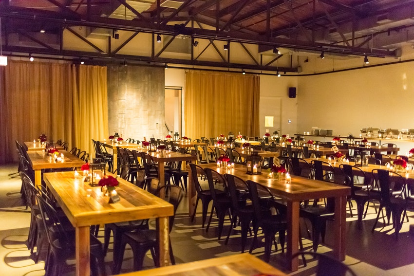 Ovation's dining room with farm tables and industrial chairs