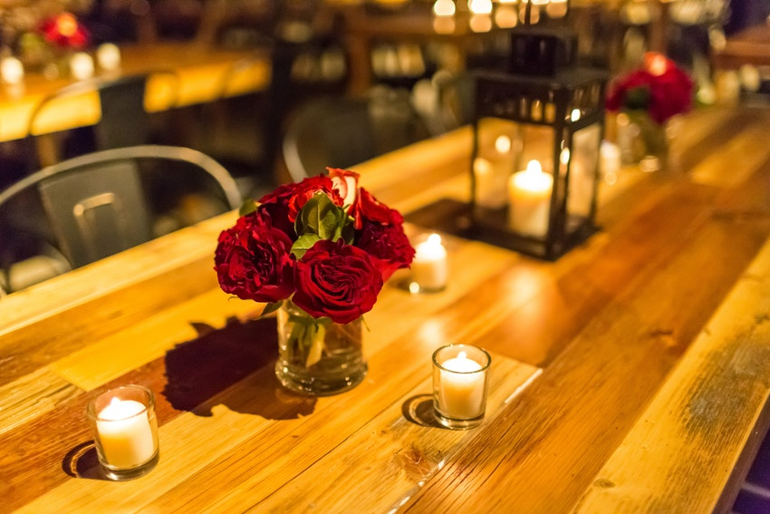 A variety of candles and vases of roses create a simple and elegant table setting on Ovation's farm tables