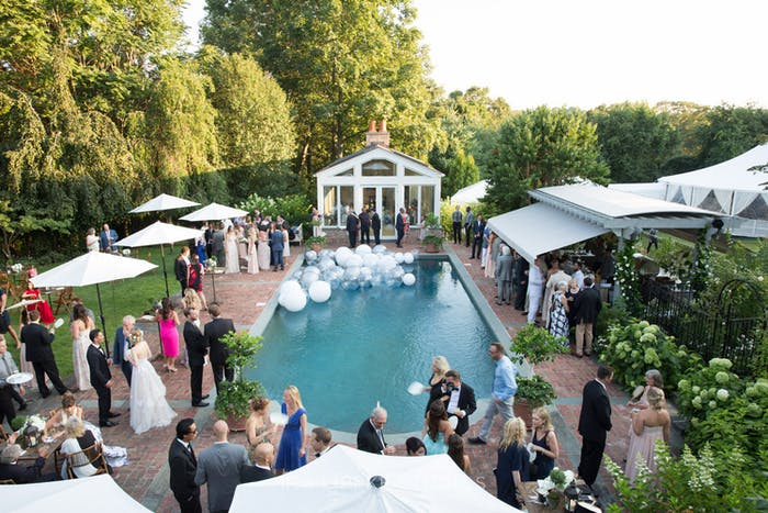 poolside cocktail parties with white umbrellas and floating orb decor