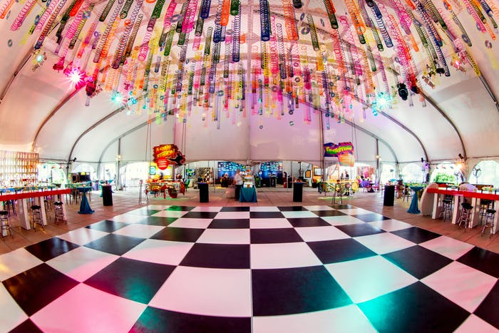 A fisheye view of a checker print dance floor with rainbow tinsel hanging above.