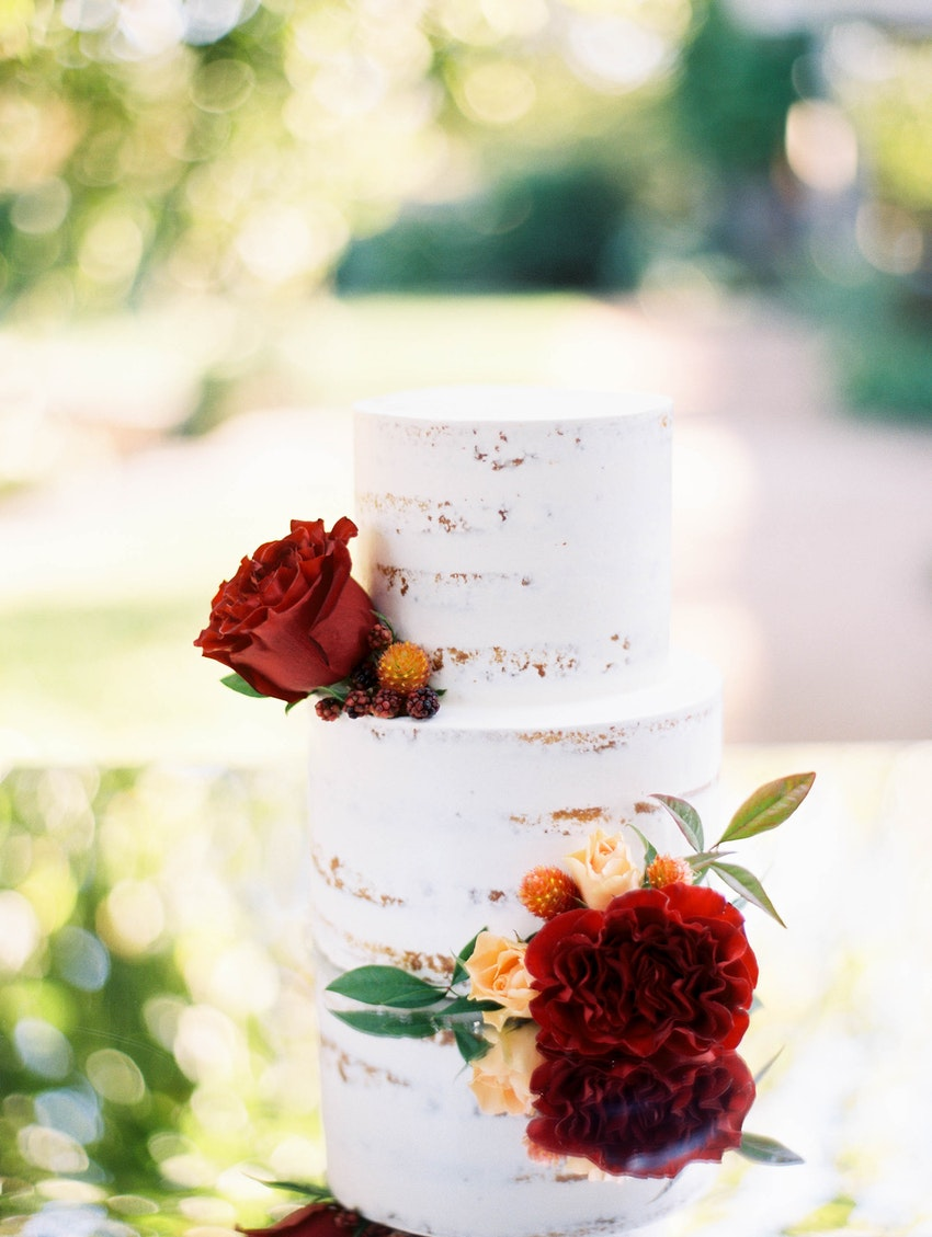 Two-tier naked cake with touches of florals set on a mirrored custom table.