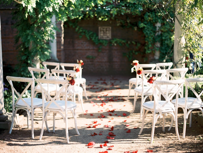 White country chairs in outdoor garden ceremony.
