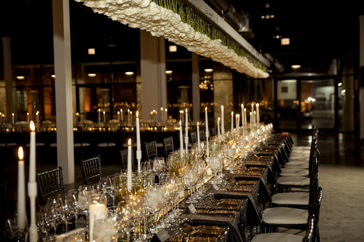 White rose chandeliers hung over the dining tables featuring 2000 roses in total. The table top glittered with sequins, candle light and gold mirror runners.