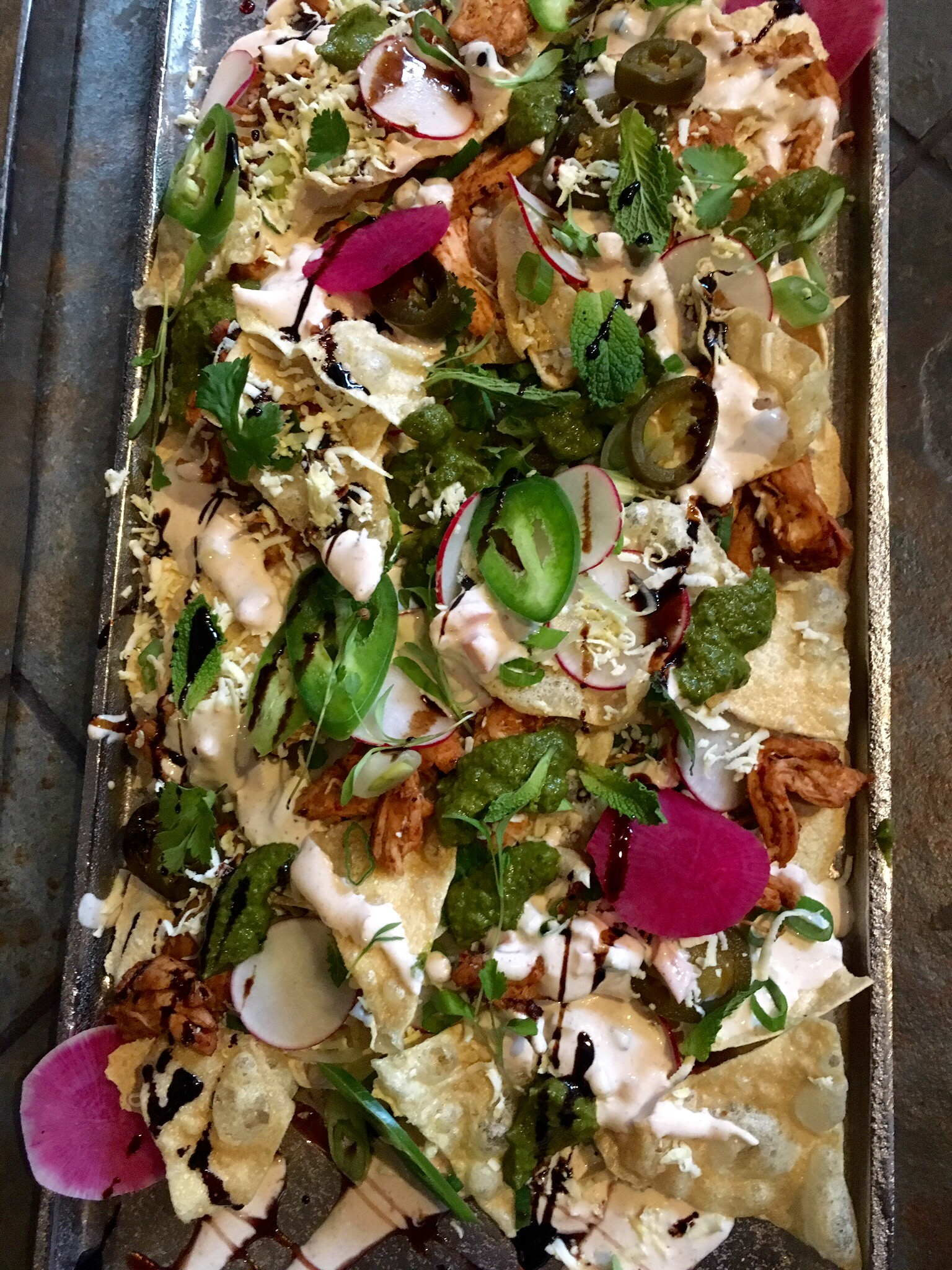 Indian Nachos Shredded Tandoori Chicken, Crispy Pappadum Chips, Yogurt Raita, Shaved Radishes, Pickled Jalapeno, Crumbled Paneer, Green Onion, Cilantro, Chimicurri or Mint Chutney